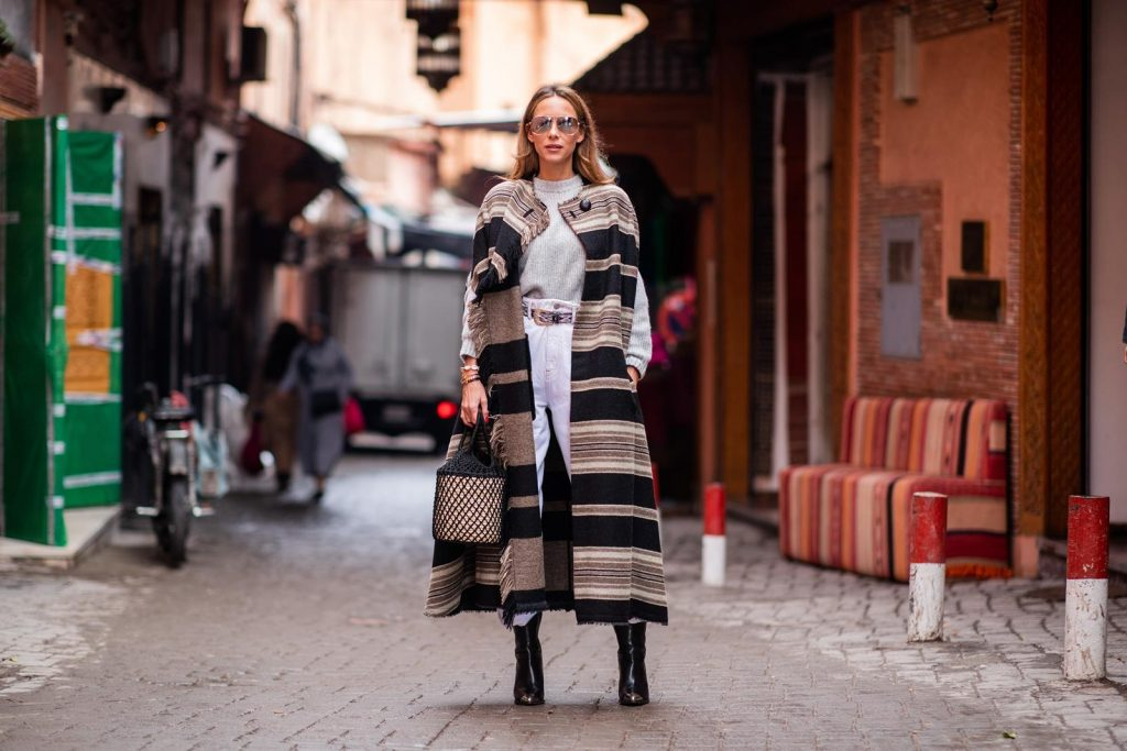 Alexandra Lapp in a Poncho Style wearing a long Huan fringed striped wool cape from Isabel Marant, an oversized grey wool sweater from H&M, white high-rise boyfriend style jeans from Isabel Marant Etoile, a black leather belt with white stitches from Isabel Marant, black Cowboy boots with a silver tip from Isabel Marant, a handwoven basket bag from Sensistudio and mirrored sunglasses from Givenchy on November 25, 2018 in Marrakech, Morocco.