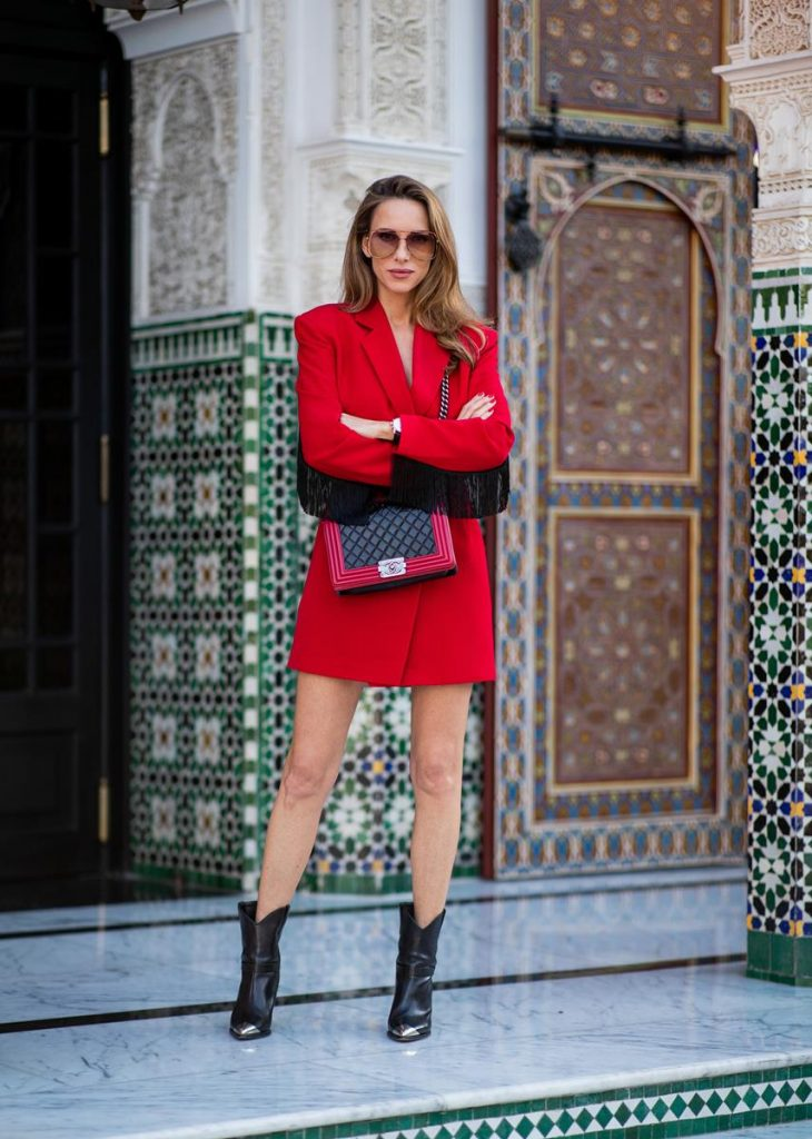 Alexandra Lapp in a red Blazer dress look wearing a red blazer dress with fringes at both arms from Pearl and Rubies, black Cowboy boots with a silver tip from Isabel Marant, red and black boy bag from Chanel and oversized sunglasses from Chloe on November 25, 2018 in Marrakech, Morocco. (Photo by Christian Vierig/Getty Images)