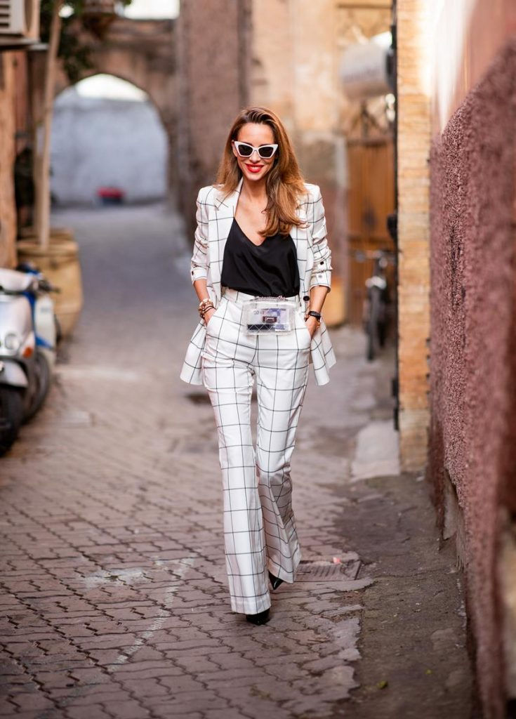 Alexandra Lapp in a ladysuit look, wearing the Pierre double-breasted checkered suit combination in black and white from Rebecca Vallance with matching high rise pants with a flared hem, a black top from Jadicted, black lacquer high heels with sparkling heels from Philipp Plein, a golden Portugieser Chronograph from IWC and a transparent waisted belt bag and white Saint Laurent New Wave 213 Lily sunglasses on November 25, 2018 in Marrakech, Morocco. (Photo by Christian Vierig/Getty Images)