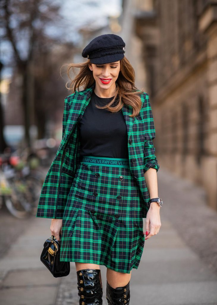 Alexandra Lapp in a checkered suit look, wearing a feminine green checkered Riani blazer with a matching pleated skirt, styled with a Vince knitted T-shirt, a black Chanel tweed baker boy cap, patent leather Louise over-the-knee boots from Christian Louboutin, and a ZAC Zac Posen patent Mini 'Eartha Iconic' bag during the Berlin Fashion Week Autumn/Winter 2019 on January 18, 2019 in Berlin, Germany. (Photo by Christian Vierig/Getty Images)