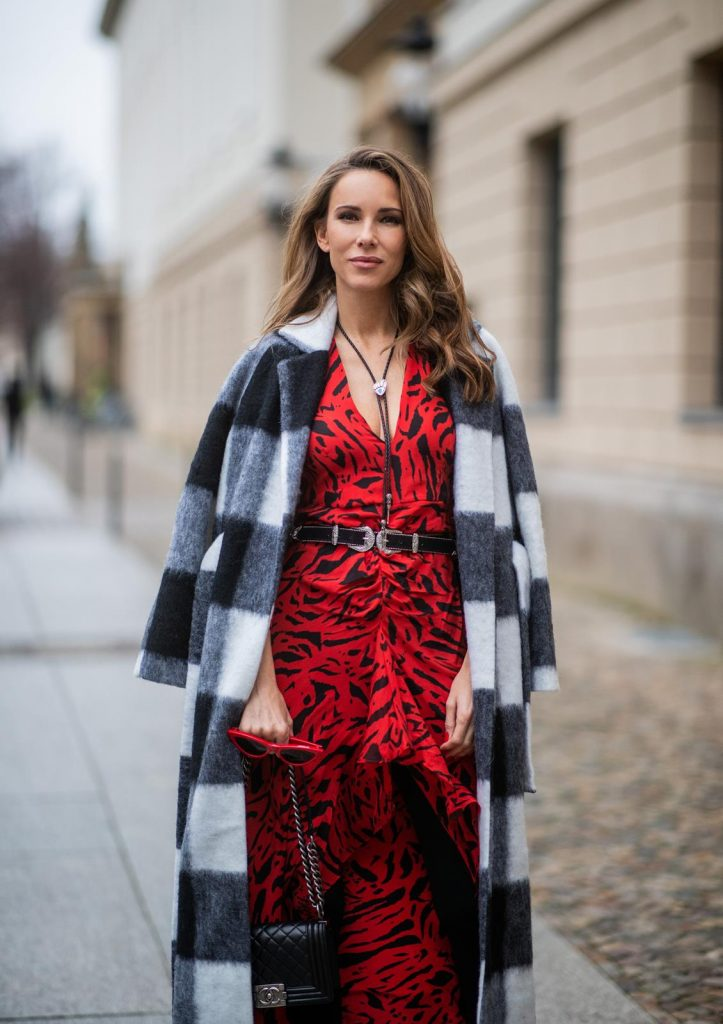 Alexandra Lapp in a Red Animal Print Look, wearing the long Adriana animal print dress from Rixo, a black and white wool coat from Ganni, the Isabel Marant Lamsy cowboy boots, a black boy bag from Chanel, a silver buckled H&M cowboy belt, a western cowboy necklace and red cat-eyed sunglasses by Celine during the Berlin Fashion Week Autumn/Winter 2019 on January 15, 2019 in Berlin, Germany. (Photo by Christian Vierig/Getty Images)