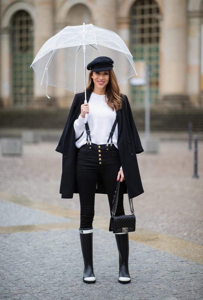Alexandra Lapp in A Chanel Rain Boots look, wearing a soft long blazer by Steffen Schraut, over a white chunky knit sweater by H&M, black skinny pants with golden buttons by Veronica Beard, styled with Chanel logo suspenders and Chanel rain boots, the Chanel Le boy bag, a Chanel tweed baker boy cap and a transparent umbrella by Mirviory during the Berlin Fashion Week Autumn/Winter 2019 on January 15, 2019 in Berlin, Germany. (Photo by Christian Vierig/Getty Images)