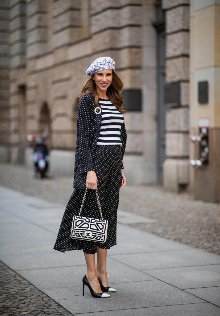 Alexandra Lapp in a tweed beret dot suit look, wearing a long black blazer with dots and matching culotte pants, black and white striped sweater with a yellow detail from Steffen Schraut, a black and white tweed beret from the Chanel La Pausa collection, a black and white 2.55 flap bag from Chanel during the Berlin Fashion Week Autumn/Winter 2019 on January 16, 2019 in Berlin, Germany. (Photo by Christian Vierig/Getty Images)