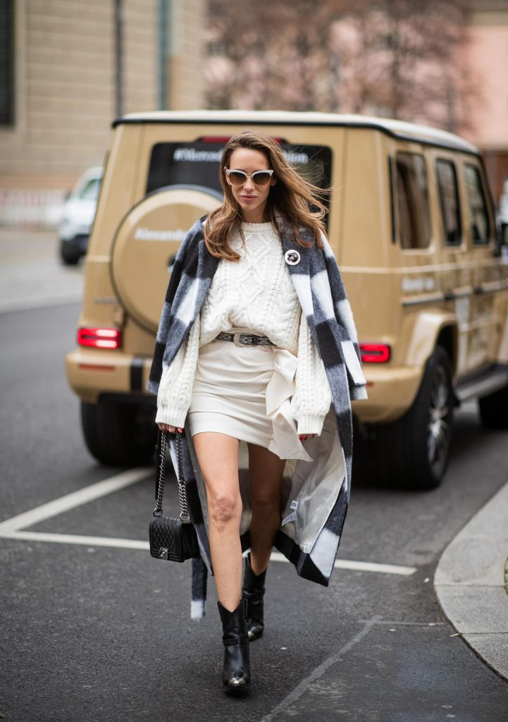 Alexandra Lapp in a Mercedes-Benz Fashion Look, in front of a Mercedes G500 wearing a black and white checked wool-blend coat from Ganni, off-white cable knit sweater from Maje, Isabel Marant ruffled skirt Nefly in off-white, embroided and silver buckled Tety belt and Lamsy ankle cowboy boots with silver tip from Isabel Marant, black Le boy bag from Chanel, Chanel brooch with Coco Chanel detail during the Berlin Fashion Week Autumn/Winter 2019 on January 16, 2019 in Berlin, Germany. (Photo by Christian Vierig/Getty Images)