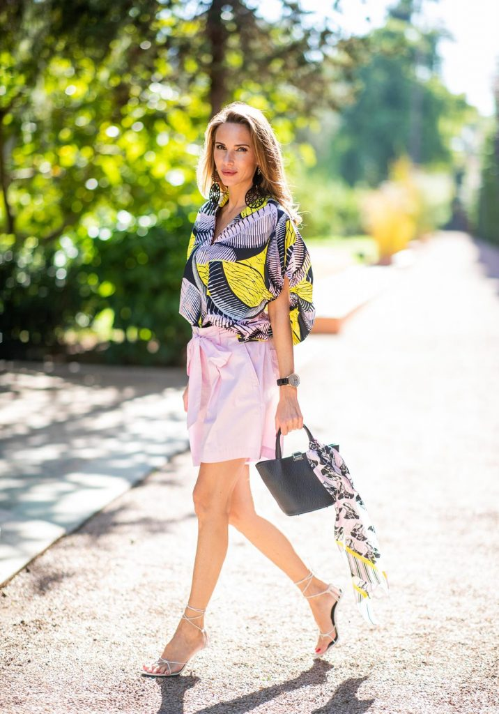 Alexandra Lapp in a Le Riad look, wearing a loose tunic blouse in a pink, yellow and black pattern with wide arms with a matching silk printed scarf and a light pink short skirt with a long bow around the waist from Marc Cain, white Inez leather sandals, black earrings from Marc Cain and black small trapeze shaped bag by Marc Cain on November 27, 2018 in Marrakech, Morocco. (Photo by Christian Vierig/Getty Images)