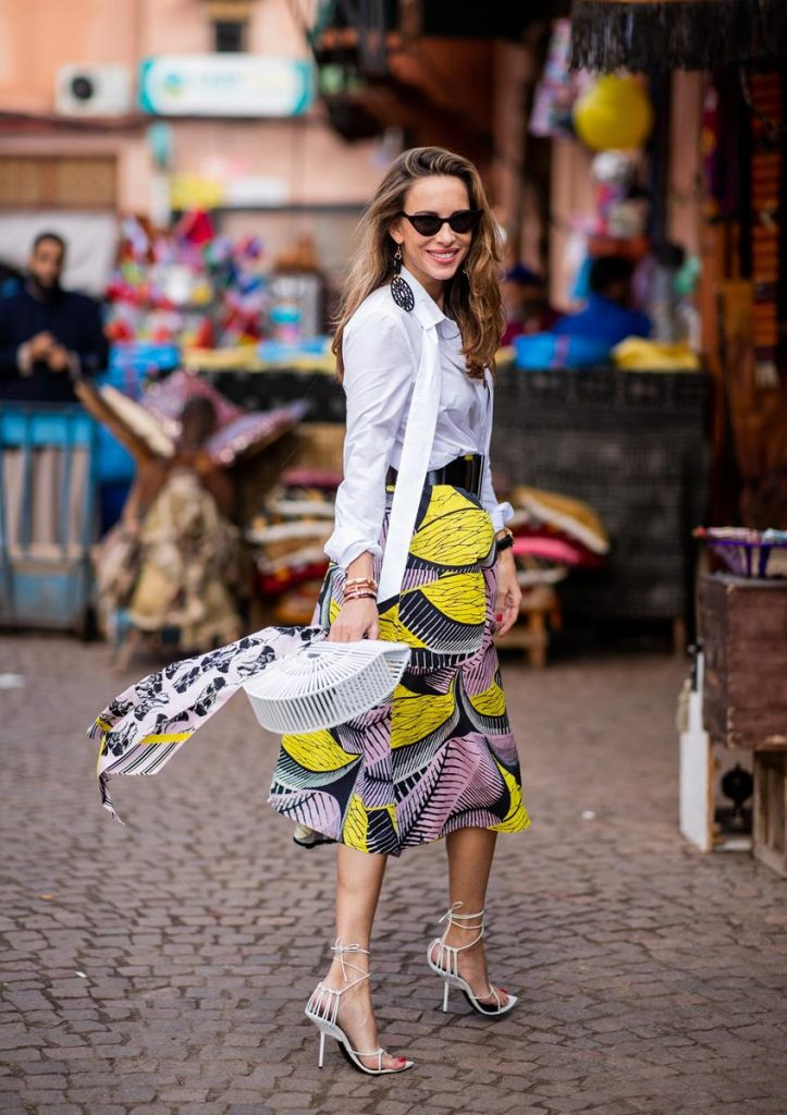 Alexandra Lapp in a Le Riad look, wearing a flared skirt printed with pink, yellow and black patterns combined with a plain bowed white shirt, a matching silk printed scarf with elephants in the same colours and round big earrings in black all by Marc Cain, leather sandals in white, white bag and black cat-eyed shaped sunglasses on November 25, 2018 in Marrakech, Morocco. (Photo by Christian Vierig/Getty Images)