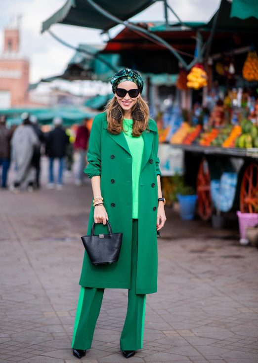Alexandra Lapp in a Le Riad look, wearing a belted long crepe Marc Cain coat in green, a neon green sweater and crepe loose-fit pants with stripes in two green tones by Marc Cain, a black small trapeze shaped bag and a printed silk scarf in multi green shades by Marc Cain, black lacquer high heels, black sunglasses and round oversized earrings in black by Marc Cain on November 26, 2018 in Marrakech, Morocco.