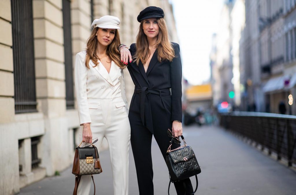 Alexandra Lapp in a Twinning Style look, wearing the white Celia overall in a smoking optic with a cut-out back from ba&sh, a white baker boy cap from Chanel, the patent Cinestripes pumps from Christian Louboutin, Gucci monogram backpack and cat-eye shaped sunglasses from Prada. Isabel Lapp is wearing a black tailored fit jumpsuit from IRO, black baker boy cap from Chanel, black Diadora Aigner backpack, cat-eye shaped sunglasses from Prada and Saint Laurent heels during Paris Fashion Week Womenswear Fall/Winter 2019/2020 on February 27, 2019 in Paris, France. (Photo by Christian Vierig/Getty Images)