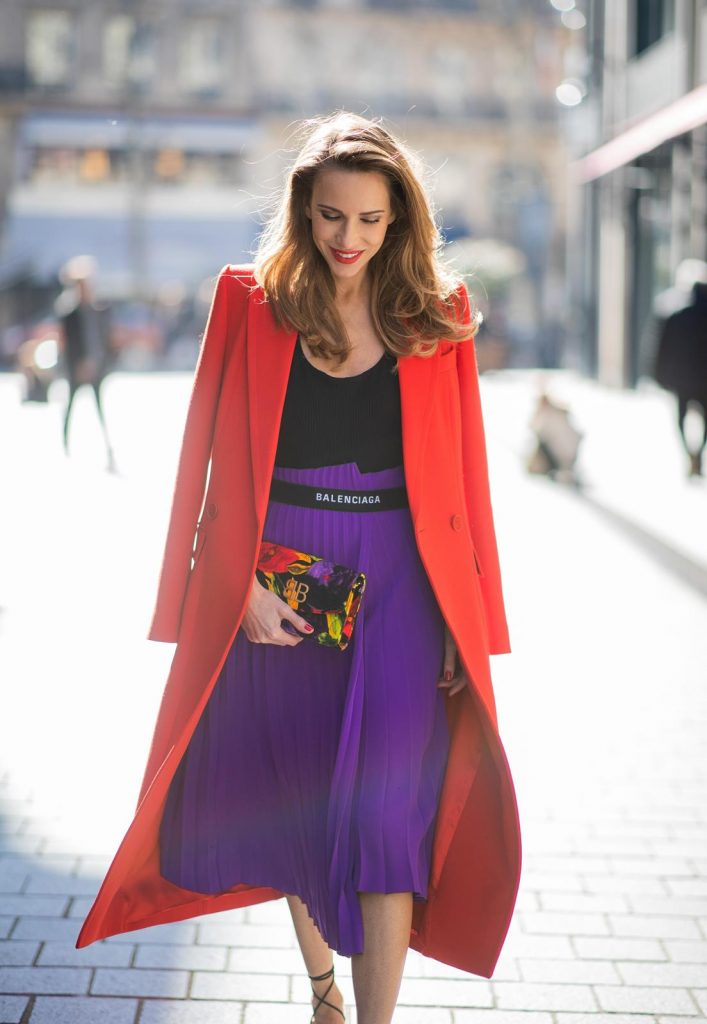 Alexandra Lapp in a Color Flash look, wearing a red Givenchy long coat, a purple Balenciaga plissée skirt, Off-white stretch top, pointed Gianvito Rossi sandals in black, Balenciaga BB printed velvet clutch all from Breuninger during Paris Fashion Week Womenswear Fall/Winter 2019/2020 on February 26, 2019 in Paris, France. (Photo by Christian Vierig/Getty Images)
