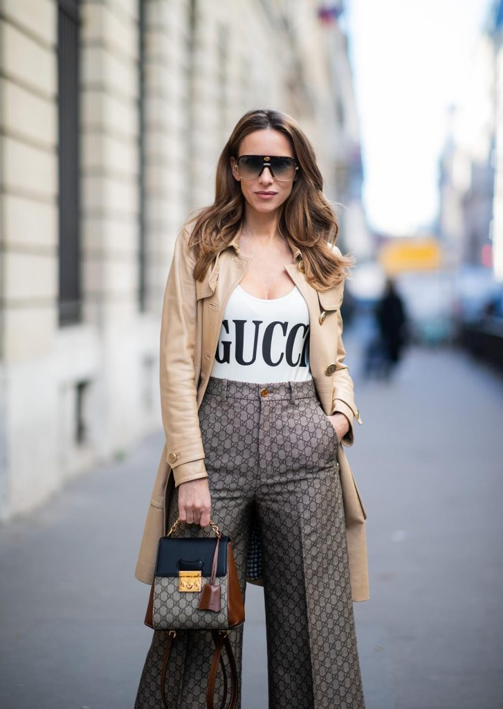 Alexandra Lapp in a Gucci culotte pants look, wearing the Culottes with monogram pattern, brown and black Gucci backpack with monogram pattern, a sparkling white swimsuit with the Gucci logo print, vintage leather Trenchcoat from Gucci, So Kate Christian Louboutin heels in cognac during Paris Fashion Week Womenswear Fall/Winter 2019/2020 on February 25, 2019 in Paris, France. (Photo by Christian Vierig/Getty Images)