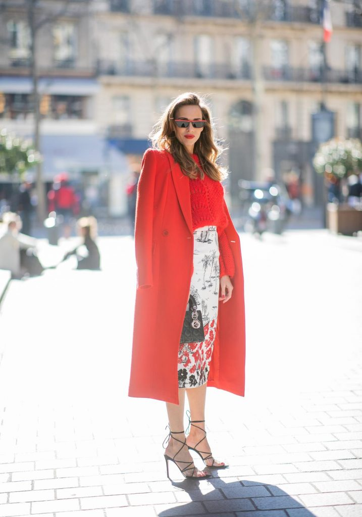 Alexandra Lapp in a Printed Skirt look, wearing a fitted two button coat in bright red from Givenchy, with a NO.21 sequined twill pencil skirt with a Palm-print, a red wool loose knit sweater from Ganni - all from Breuninger, black sandals from Gianvito Rossi, Prada cat-eye shaped sunglasses with red details and the Lady Dior mini bag during Paris Fashion Week Womenswear Fall/Winter 2019/2020 on February 26, 2019 in Paris, France. (Photo by Christian Vierig/Getty Images)
