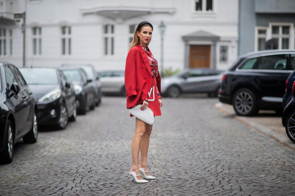 Alexandra Lapp in a Valentino Look, wearing a short red wool skirt with the embroidered V Logo, with a matching long oversized blazer, a logo printed twill shirt in blue white and red- all from Valentino, a black silk satin headband from Prada on May 01, 2019 in Duesseldorf, Germany. (Photo by Christian Vierig/Getty Images)
