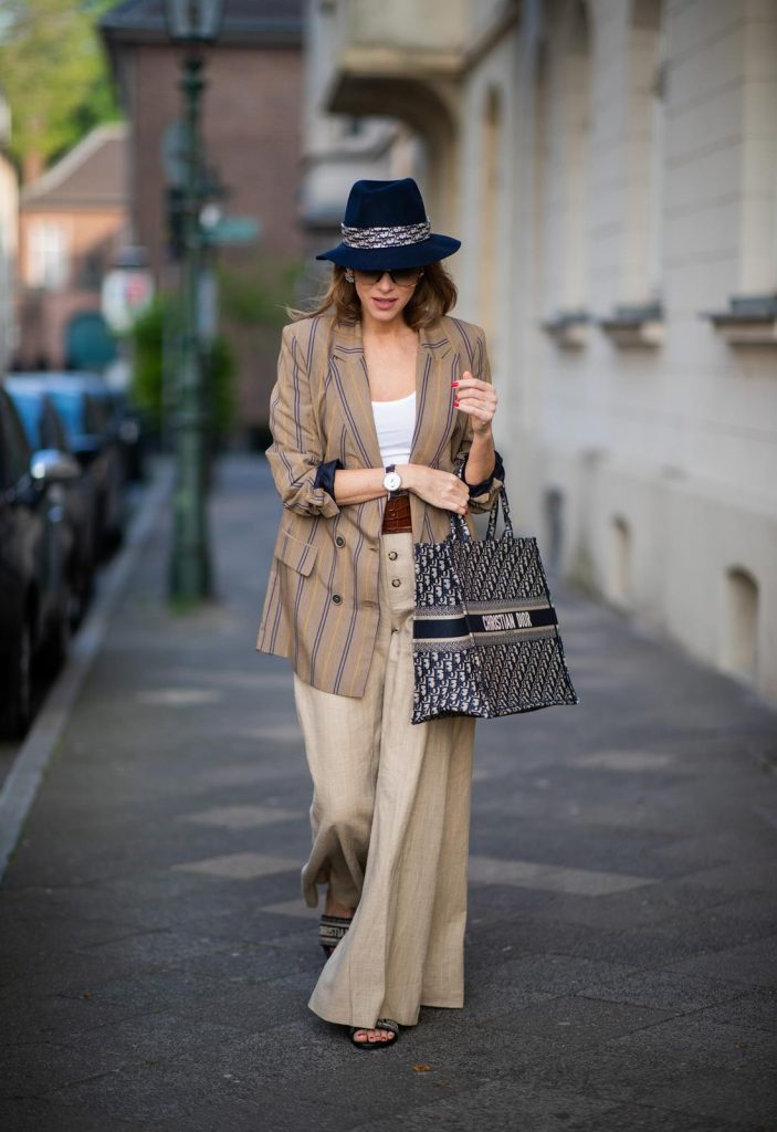 Alexandra Lapp is seen wearing a beige brown long striped blazer from Zara, white tank top from H&M, waisted belt from Max Mara, high waisted wide leg pants from Staud, Dior Book Tote Dior Oblique bag and a Dior foulard on a blue Borsalino hat on May 04, 2019 in Duesseldorf, Germany. (Photo by Christian Vierig/Getty Images)