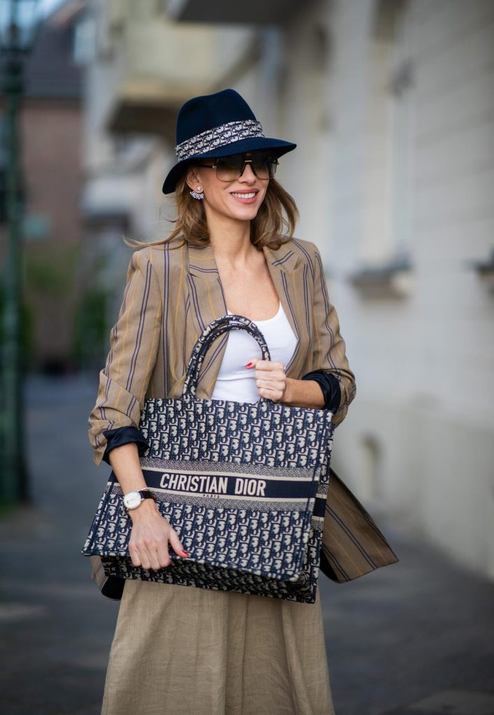 Alexandra Lapp in a Dior Book Tote Bag Look, wearing a beige brown long striped blazer from Zara, white tank top from H&M, waisted belt from Max Mara, high waisted wide leg pants from Staud, Dior Dway mules, Dior Book Tote Dior Oblique bag and a Dior foulard on a blue Borsalino hat on May 04, 2019 in Duesseldorf, Germany. (Photo by Christian Vierig/Getty Images)