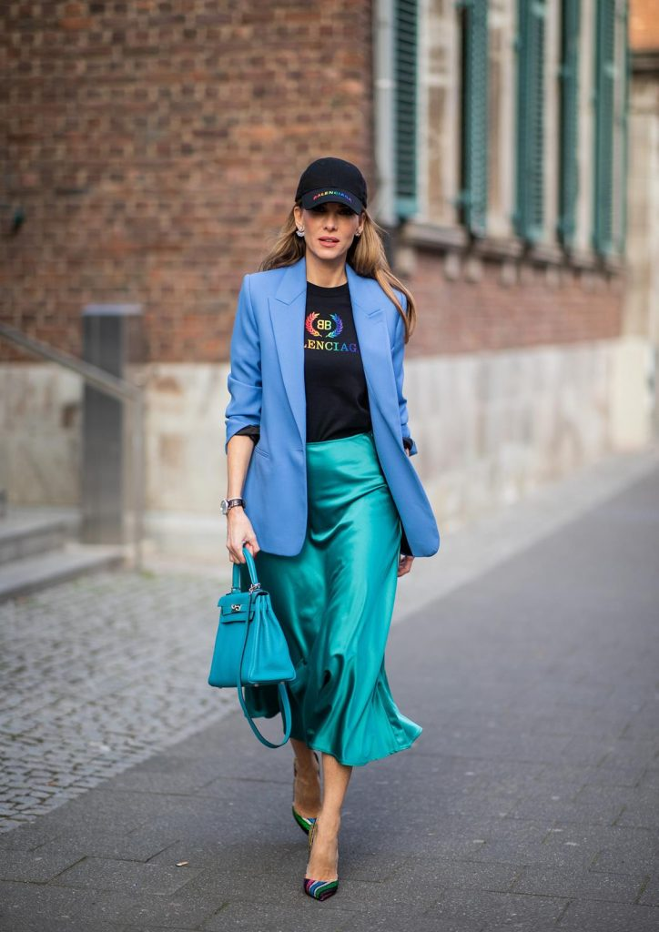 Alexandra Lapp is seen wearing a long turquoise satin skirt from Zara, a black logo print t-shirt from Balenciaga, blue oversized blazer from Zara, black base cap with logo print in rainbow colors from Balenciaga and a turquoise Hermès Kelly bag. on May 04, 2019 in Duesseldorf, Germany. (Photo by Christian Vierig/Getty Images)