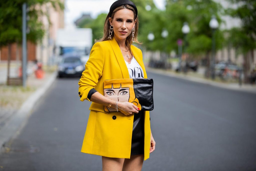 Alexandra Lapp is seen wearing a yellow oversized Zara Blazer, black leather skirt from Balmain, printed vintage Prada clutch, black silk Prada headband and long Chanel earrings and Vogue t-shirt during Berlin Fashion Week on July 02, 2019 in Berlin, Germany. (Photo by Christian Vierig/Getty Images)