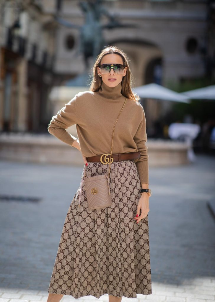 PARIS, FRANCE - SEPTEMBER 23:Blogger, Model and Influencer Alexandra Lapp is seen wearing a Gucci GG pleated jersey midi skirt, GG Marmont Mini-Bucket bag in nude, Christian Louboutin So Kate pumps in camel, camel Nili Lotan sweater, beige Zara trenchcoat during Paris Fashion Week Womenswear Spring Summer 2020 on September 23, 2019 in Paris, France.
