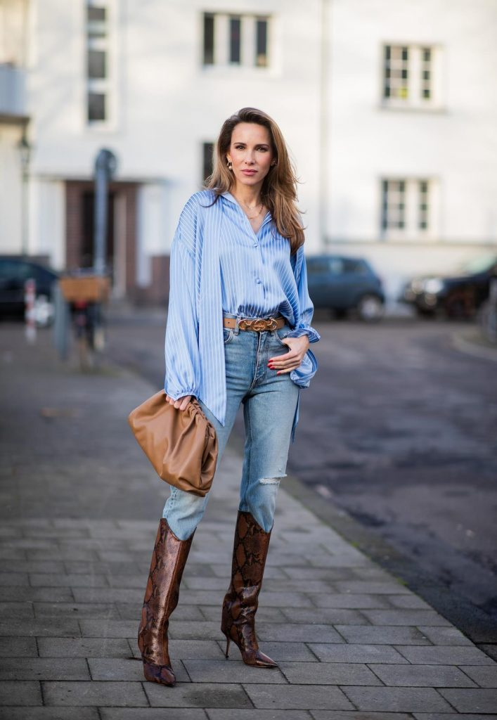 DUESSELDORF, GERMANY - DECEMBER 10: Alexandra Lapp is seen wearing brown Zara teddy coat, oversized blue striped button shirt Balenciaga, brown Gucci belt, light blue ripped denim jeans Celine, brown Pouch bag Bottega Veneta, brown Jimmy Choo boots with snake print on December 10, 2019 in Duesseldorf, Germany.