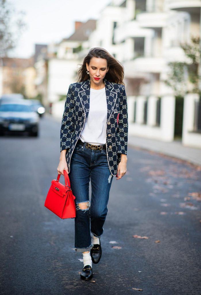 DUESSELDORF, GERMANY - DECEMBER 11: Alexandra Lapp is seen wearing a college look, dark denim blue jeans AG Jeans, white sleeveless muscle tshirt with padded shoulders The Frankie Shop, Gucci GG horsebit leather belt, Gucci college jacket with logo print, red Hermes Kelly bag on December 11, 2019 in Duesseldorf, Germany. (Photo by Christian Vierig/Getty Images)
