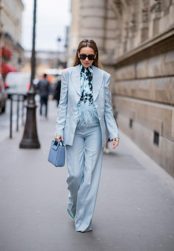 PARIS, FRANCE - FEBRUARY 25: Alexandra Lapp is seen wearing a suit style, light blue De La Vali suit, blue Shirley mini bag from Staud, 16Arlington satin top with feathers, Prada pumps in light blue, square-frame black Bottega Veneta sunglasses all from Net-A-Porter during Paris Fashion Week - Womenswear Fall/Winter 2020/2021 : Day Two on February 25, 2020 in Paris, France.