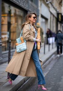 PARIS, FRANCE - FEBRUARY 25: Alexandra Lapp is seen wearing Jeans Jane Flare from Celine, double breasted trench coat from Valentino, Stella McCartney blouse, Bottega Veneta Padded Cassette leather bag in light blue, Bottega Veneta sunglasses - all from Breuninger during Paris Fashion Week - Womenswear Fall/Winter 2020/2021