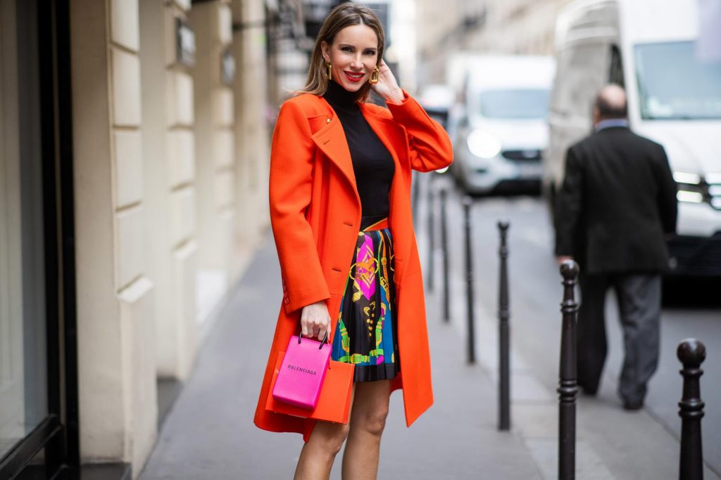 PARIS, FRANCE - FEBRUARY 26: Alexandra Lapp is seen wearing a Givenchy coat in orange, pleated silk skirt from Versace, turtleneck pullover in black from Dorothee Schumacher, slingback pumps in orange from The Attico, Balenciaga Tote Shopping Phone bag, Medea Vinile Short bag during Paris Fashion Week - Womenswear Fall/Winter 2020/2021 : Day Three on February 26, 2020 in Paris, France.