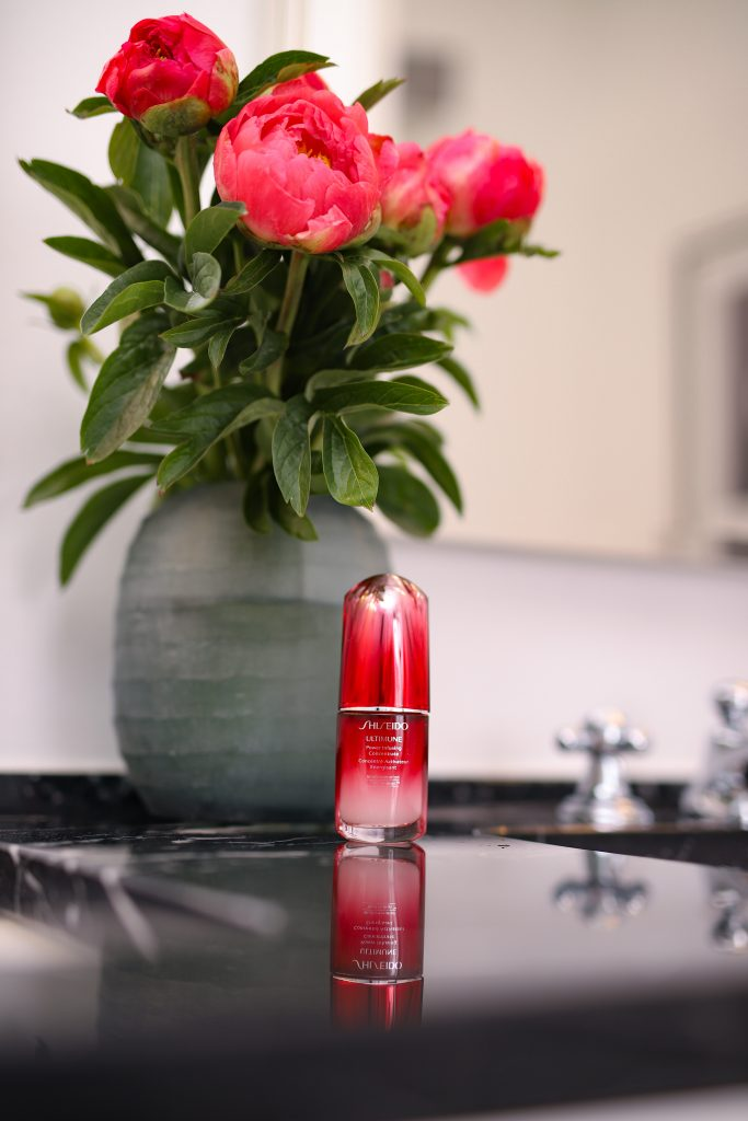 Alexandra Lapp is massaging the SHISEIDO Ultimune Power Infusing Concentrate into her skin.
