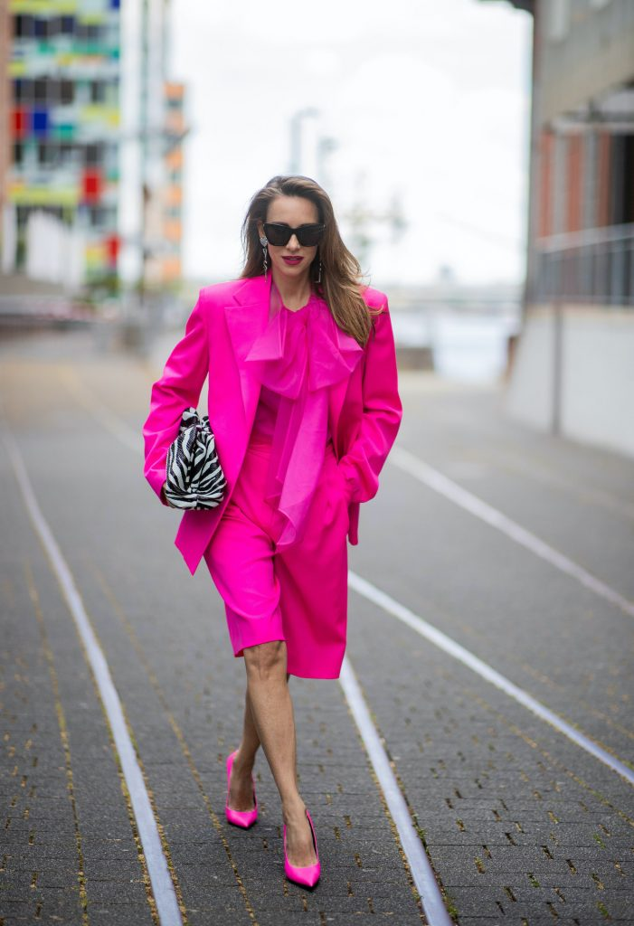 Alexandra Lapp is seen wearing pink blazer by Valentino, shorts and Valentino silk blouse with a bow - all in pink, Square Knife pumps in neon pink from Balenciaga, Saint Laurent earrings with a heart and YSL letters and Bottega Veneta Clutch The Pouch with Zebra pattern all styles from Breuninger.