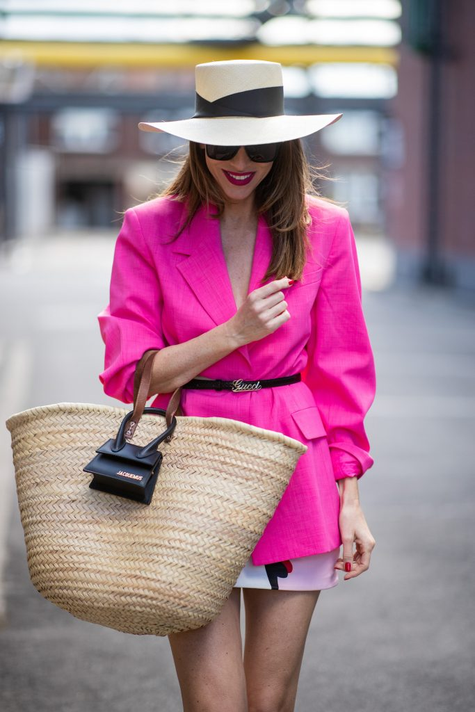Alexandra Lapp is seen wearing an oversized pink blazer from H&M, Gucci waist belt, Sensi Studio straw hat, Sensi Studio straw bag in combination with Tote Le Chiquito Mini bag from Jacquemus, Parabel Gurung mini leather skirt, Cult Gaia sandals in black.