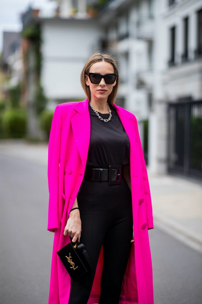 Alexandra Lapp is seen wearing Saint Laurent stretch knit stirrup leggings in black, black oversize t-shirt with shoulder pads from H&M, Dolce Gabbana waist belt in black, Square Knife pumps in neon pink from Balenciaga, double breasted oversize coat and pink blazer from The Attico in pink, Saint Laurent Monogram Clutch in black and Tiffany City HardWear necklace in sterling silver.