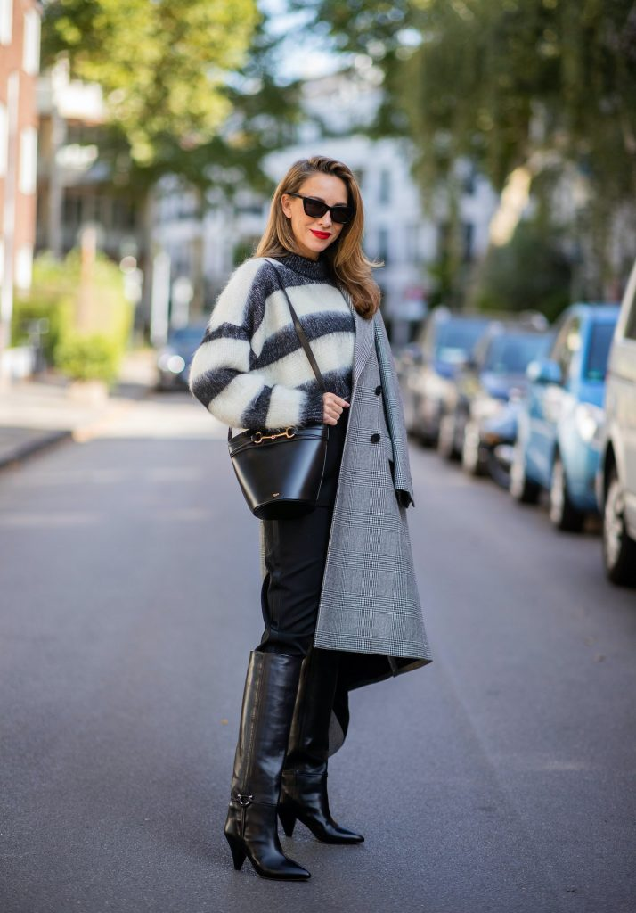 Alexandra Lapp is seen wearing Alexander McQueen coat with prince of wales check, SAINT LAURENT striped mohair-blend sweater, SAINT LAURENT high waist pants in black, CELINE Bucket Crécy bag in black and Isabel Marant pointed-toe knee-high autumn boots in black. All looks by Breuninger.