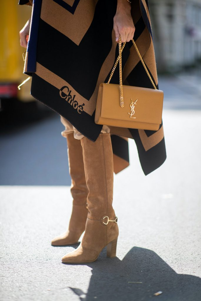 Alexandra Lapp is seen wearing Chloé striped wool cape, Chloé chunky-knit sleeveless jumper in camel, Chloé linen cargo pants in beige, SAINT LAURENT Kate medium bag in camel and CELINE Claude calfskin autumn boots in sand. All looks by Breuninger.