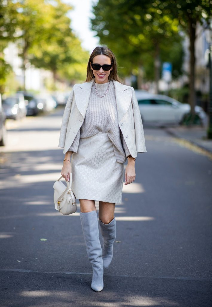 Alexandra Lapp is seen wearing Gucci monogram lamé jacket in off-white and silver, IRIS von ARNIM short cashmere sweater in alabaster, Gucci monogram lamé skirt in off-white and silver, CELINE Besace 16 bag in cream and AQUAZZURA Gainsbourg suede autumn boots in light grey. All looks by Breuninger.