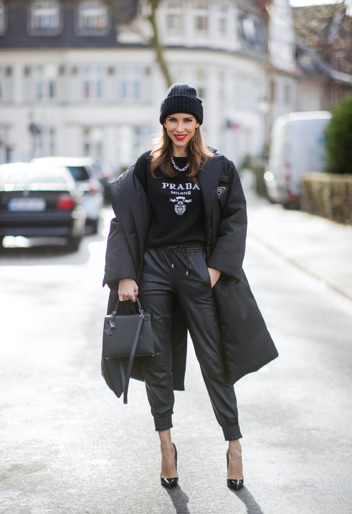 Alexandra Lapp is seen wearing one of her puffer jackets, PRADA Piumino nylon coat in black, PRADA knitted logo jumper in black, TIFFANY&CO. City HardWear necklace in sterling silver, SET leather joggers in black, XX knitted beanie, HERMÈS Kelly 28 bag in black, CHRISTIAN LOUBOUTIN So Kate pumps in black.