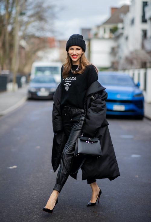 Alexandra Lapp is seen wearing PRADA Piumino nylon coat in black, PRADA knitted logo jumper in black, TIFFANY&CO. City HardWear necklace in sterling silver, SET leather joggers in black, XX knitted beanie, HERMÈS Kelly 28 bag in black, CHRISTIAN LOUBOUTIN So Kate pumps in black.