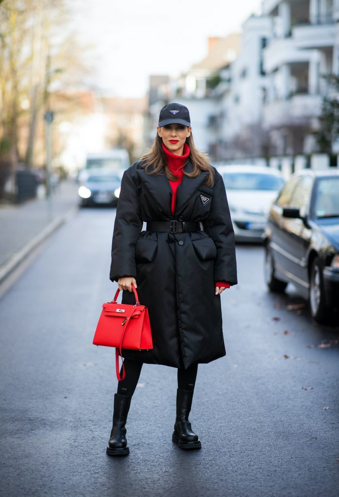 Alexandra Lapp is seen wearing one of her puffer jackets, PRADA Piumino nylon coat in black, PRADA nylon cap in black FALCONERI cashmere turtle neck dress, HERMÈS Kelly 28 bag in red, and BOTTEGA VENETA The Lug boots in black.