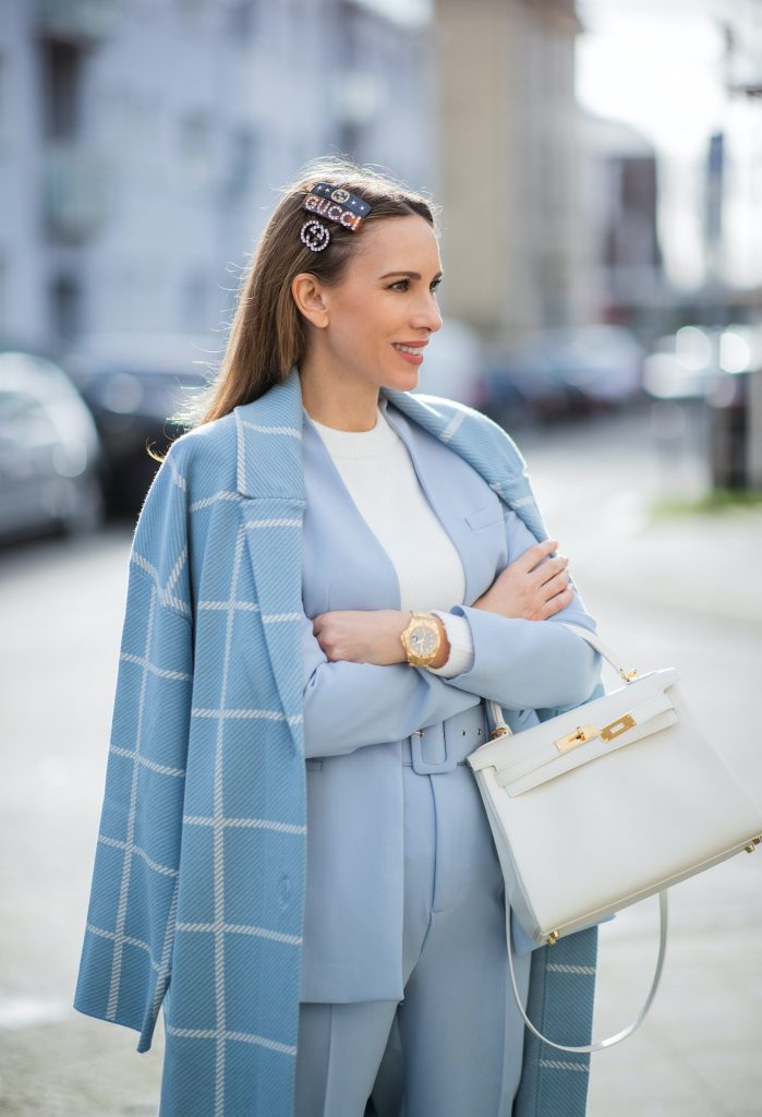 Alexandra Lapp is seen wearing pastel suits from ZARA checked coat in ligth blue, ZARA blazer in pastel blue, ZARA knit jumper in white, ZARA pants in pastel blue, GUCCI hair clips, HERMÈS Kelly 28 bag in white, GUCCI loafers in silver and white