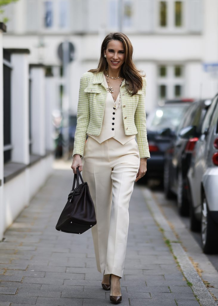 Alexandra Lapp is seen wearing Chanel jacket, Chanel jewelry, Christian Dior vest and trousers, Hermès Birkin Bag, Christian Louboutin So Kate pumps. Complete look by SuperBrands Secondhand.