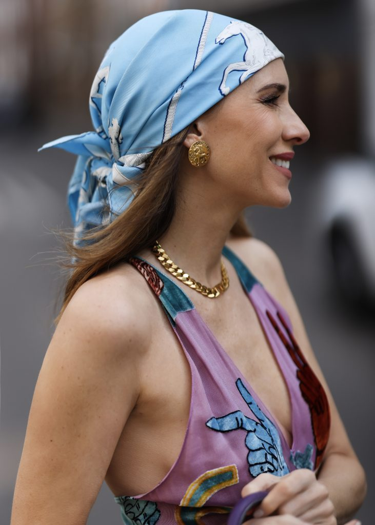 Alexandra Lapp is seen wearing Maison Valentino dress, Hermès silk scarf, Christian Dior necklace, Chanel ear clips and bracelet, Hermès Birkin Bag and Bottega Veneta sandals. Complete look by SuperBrands Secondhand.